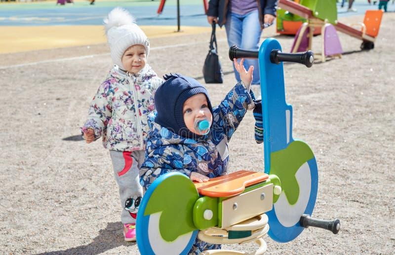 De kleine kinderen spelen op de speelplaats Kindontwikkeling kinderen` s spelen Vermaak voor kinderen stock foto