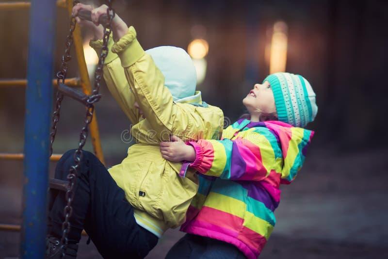 De kleine kinderen spelen in speelplaats in avond in park op achtergrond van het glanzen lichten royalty-vrije stock afbeelding