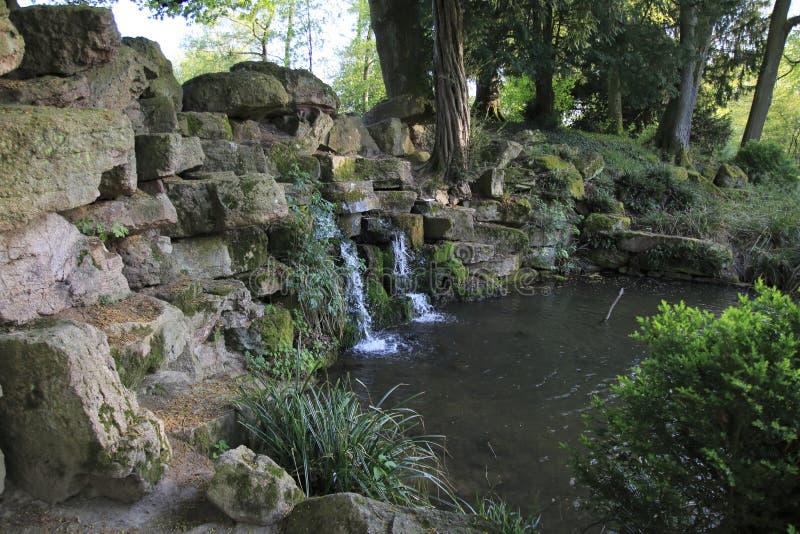 De kleine kreek, rivier valt over een kleine waterval, over stenen, in een meer stock fotografie