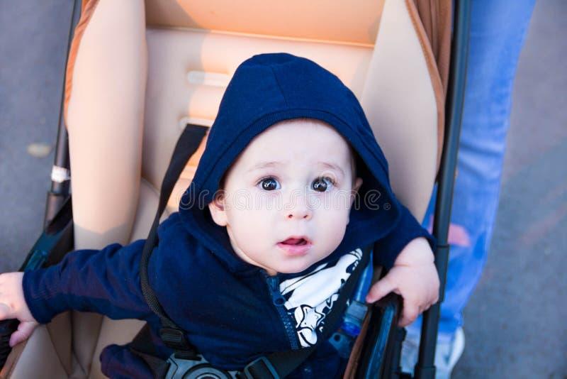 De kleine leuke pasgeboren zitting van de babyjongen in een vervoer in warme de winterkleren met fopspeen, concept het baren van  stock foto's
