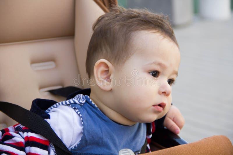 De kleine leuke pasgeboren zitting van de babyjongen in een vervoer in warme de winterkleren met fopspeen, concept het baren van  royalty-vrije stock fotografie