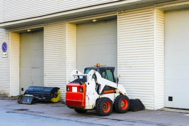 de kleine minitractor met een blad en een emmer voor straat het schoonmaken is bij de poort van een grote garage stock fotografie