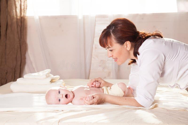 De kleine moeder die van de jongensbaby massagehanden en benen doen stock foto's