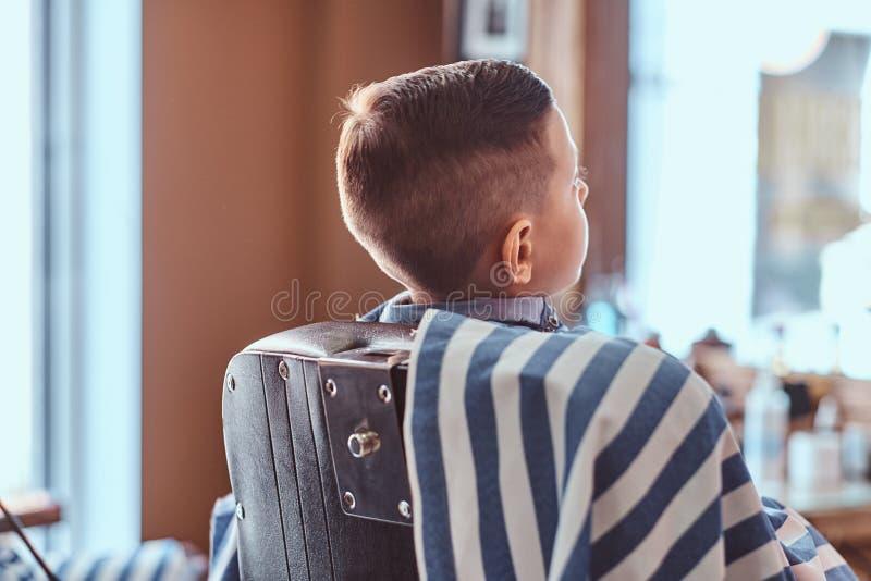 De kleine mooie jongen toont zijn nieuw kapsel terwijl het zitten bij herenkapper stock fotografie