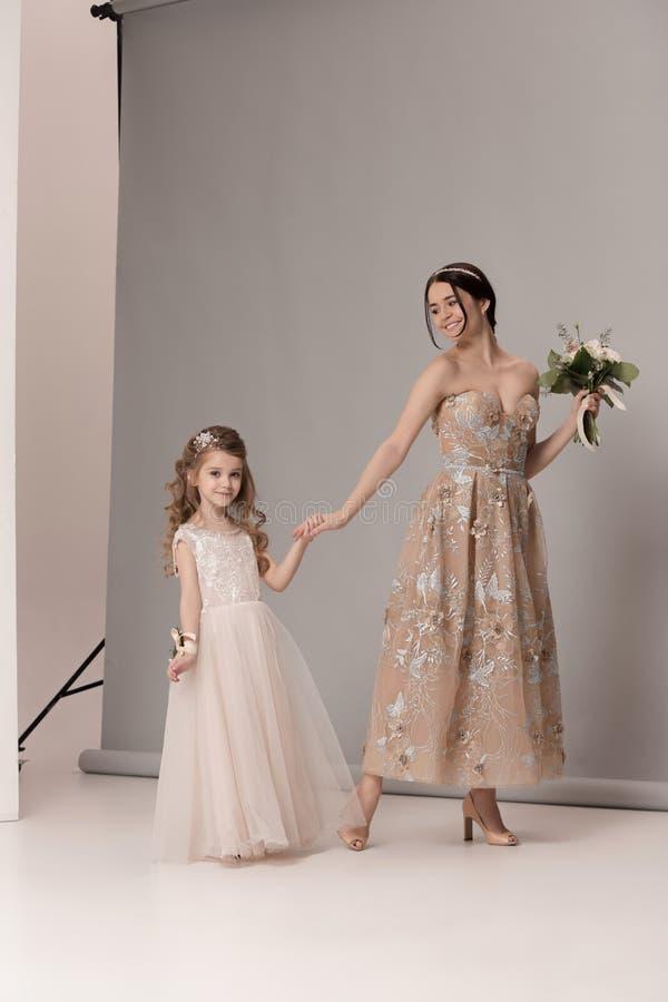 De kleine mooie meisjes met bloemen kleedden zich in huwelijkskleding royalty-vrije stock foto