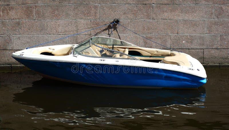 De kleine motorboot wordt vastgelegd aan de granietmuur royalty-vrije stock afbeeldingen