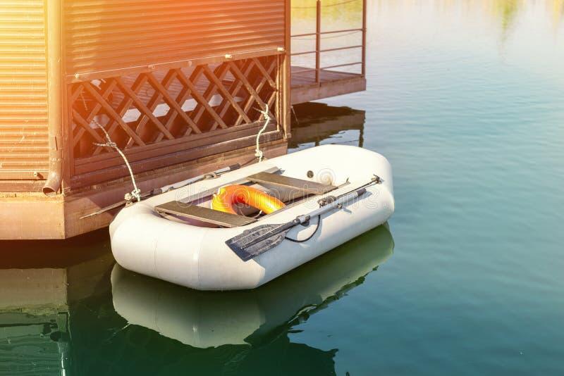 De kleine opblaasbare rijboot met peddels legde dichtbij houten gazebo op pijler vast Vissersboot die bij meer of rivierkust vroe royalty-vrije stock afbeelding