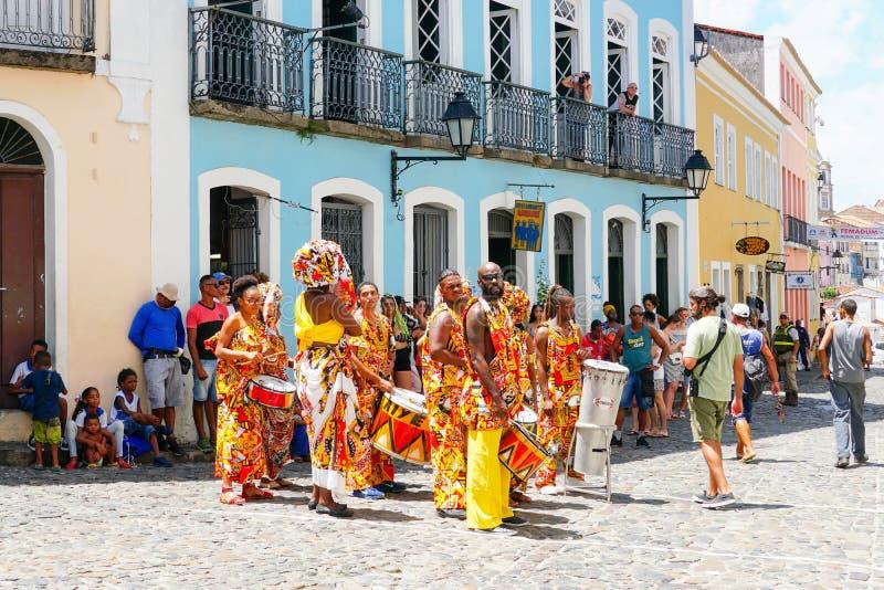 De kleine parade van de danser met traditionele kostuums en instrumenten die met feestneuzen vieren Carnaval, Brazilië stock foto