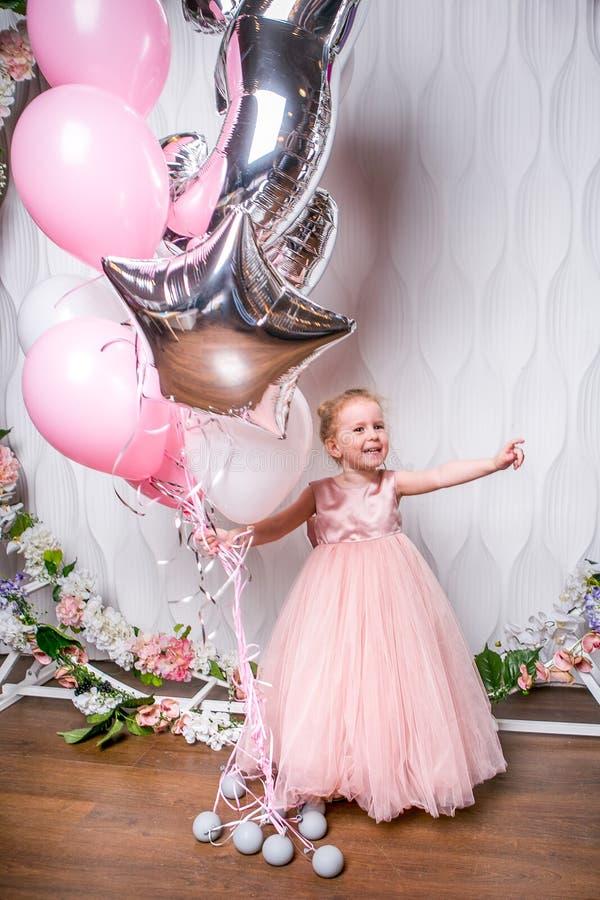 De kleine prinses in een mooie roze kleding houdt ballons, lach en punten aan de zij, lichte achtergrond royalty-vrije stock afbeelding