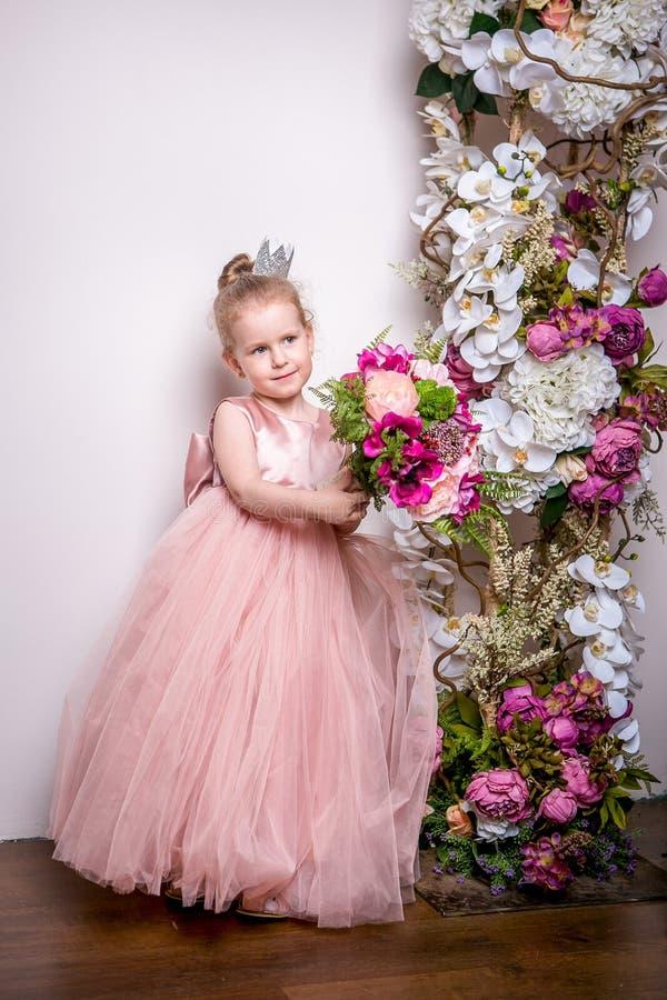 De kleine prinses in een mooie roze kleding houdt een boeket van pioenen, magnolia, bessen en groen op de achtergrond van FL royalty-vrije stock fotografie