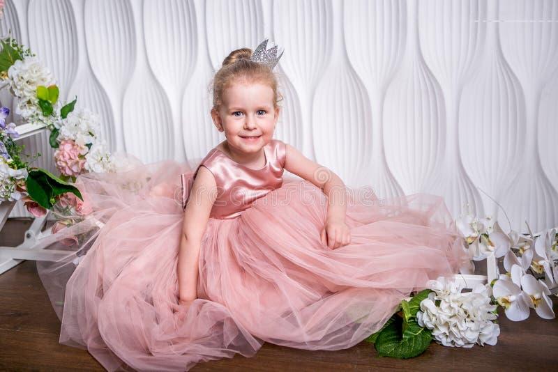 De kleine prinses in een mooie roze kleding zit op de vloer dichtbij de bloemboog op een lichte achtergrond en glimlacht royalty-vrije stock foto's