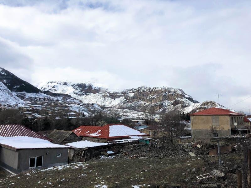 De kleine steenhuizen, gebouwen in het dorp op de mooie berg koude winter nemen met de de hoge mist en sneeuw van bergpieken zijn royalty-vrije stock foto's
