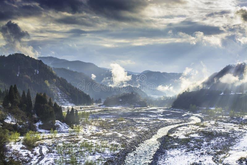 De kleine stroom stroomt tussen berg wat door sneeuw en lichte verspreiding behandelen stock afbeelding