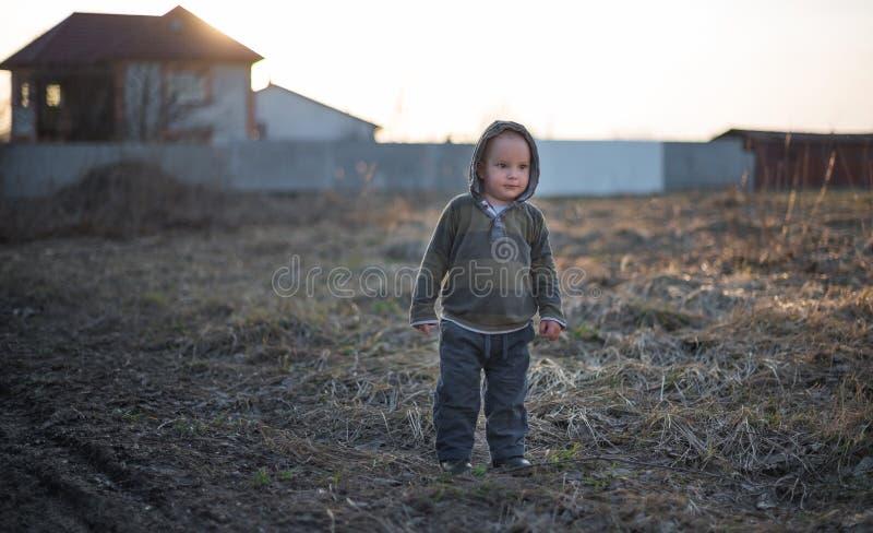 De kleine twee-jaar-oude jongen bevindt zich op de aarde stock afbeeldingen