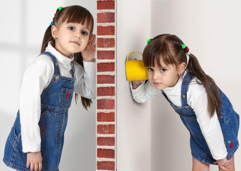 De kleine tweelingmeisjes luistert af stock fotografie