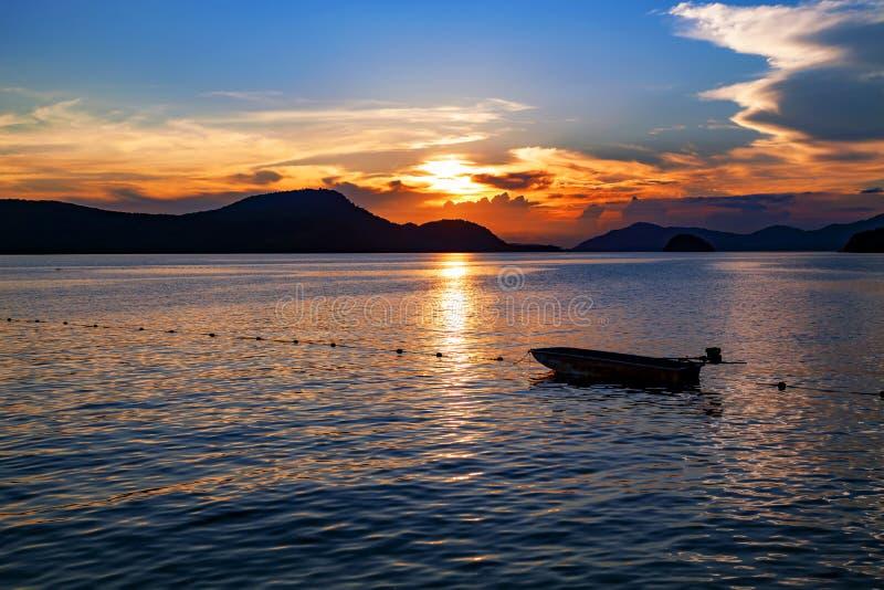 De kleine vissersboot in het overzeese zonsonderganglandschap, het Mooie Landschap en het licht van aard in avond met mooie kleur royalty-vrije stock afbeelding