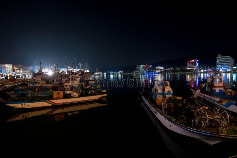 De kleine vissersboten van de nachthaven met stadshorizon bij nacht stock fotografie