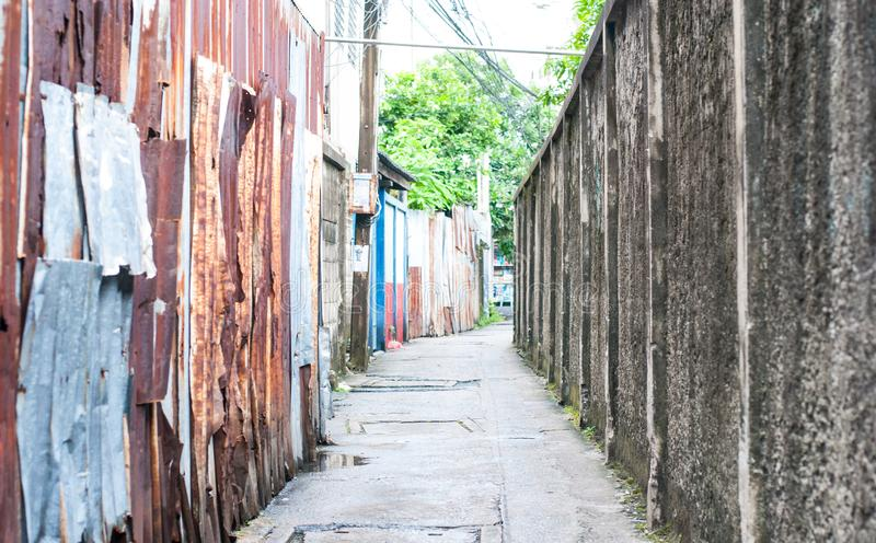 De kleine weg in een steeg in Bangkok, Thailand, linkerkant is roest stock foto