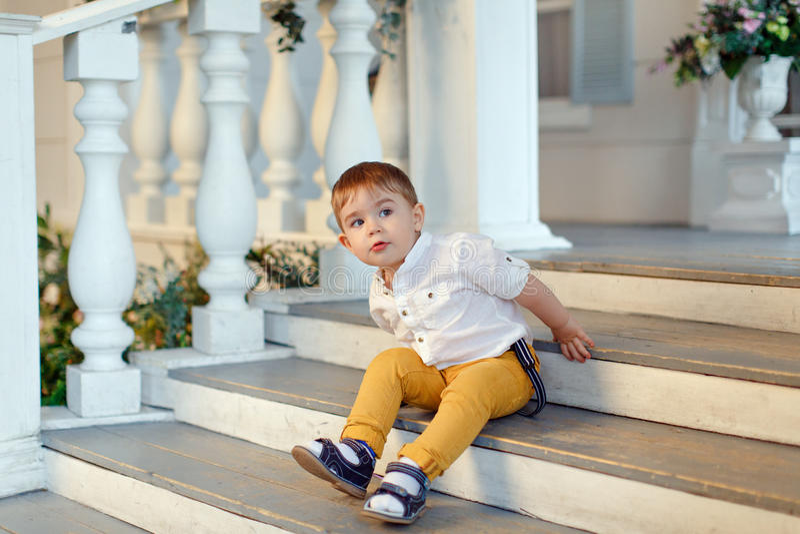 De kleine zeer leuke, charmante jongen in gele broeken zit op sta royalty-vrije stock fotografie