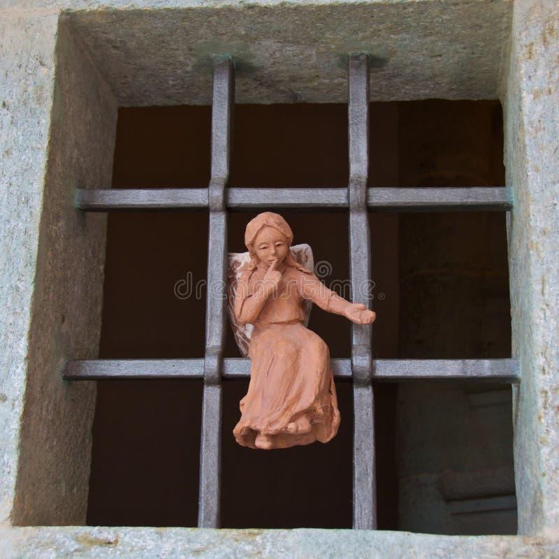 De kleine zitting van het engelenstandbeeld op het venster om mensen eraan te herinneren om in kerk stil te houden stock foto