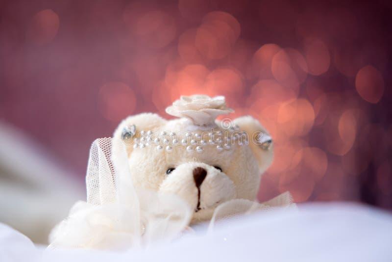 De kleine zitting van de teddybeerpop op wit tapijt met achtergrond van de onduidelijk beeld de roze kleur bokeh stock afbeeldingen