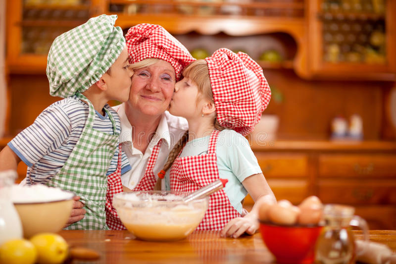 De kleinzoon en de kleindochter kussen hun grootmoeder in de keuken stock afbeelding