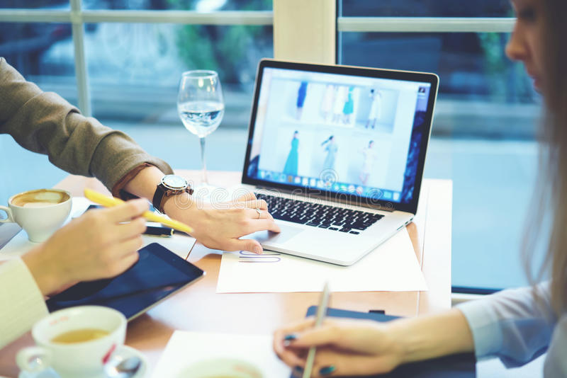 De kleren die van meisjesontwerpers samen gebruikend laptop computer met spot op het scherm verbonden met 5G radio in koffie werk stock foto's