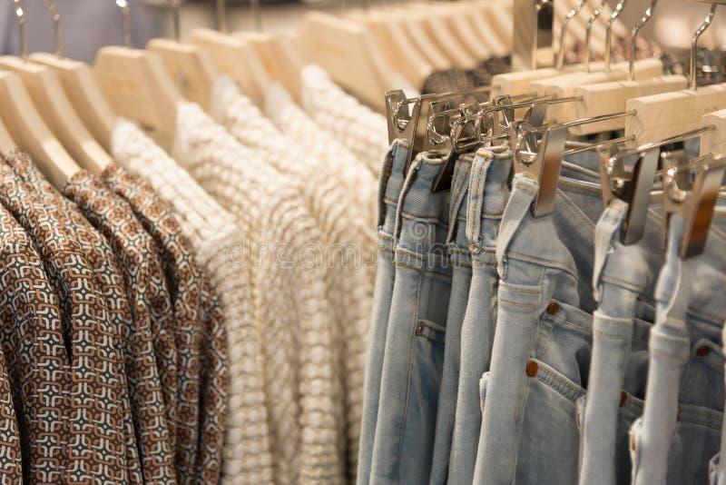De kleren en de jeans van vrouwen hangen op hangers in opslag royalty-vrije stock fotografie