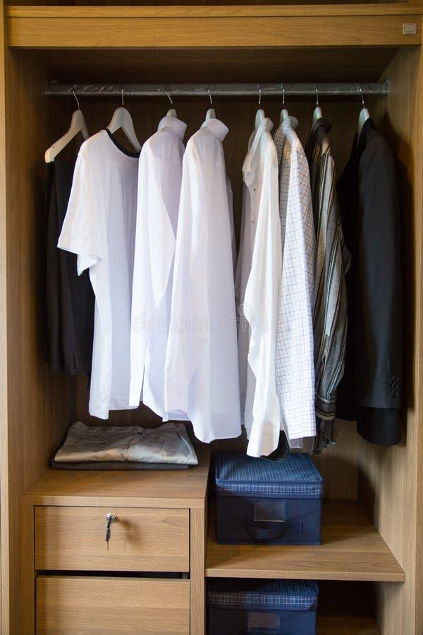 De kleren hangen op een plank in een ontwerper kleden opslag, moderne kast met rij van doeken die in garderobe, uitstekende ruimt stock afbeeldingen