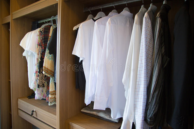 De kleren hangen op een plank in een ontwerper kleden opslag, moderne kast met rij van doeken die in garderobe, uitstekende ruimt stock afbeelding