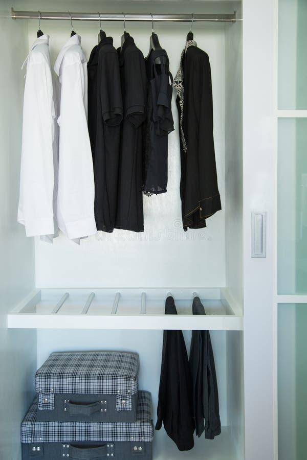 De kleren hangen op een plank in een ontwerper kleden opslag, moderne kast met rij van doeken die in garderobe, uitstekende ruimt stock foto's