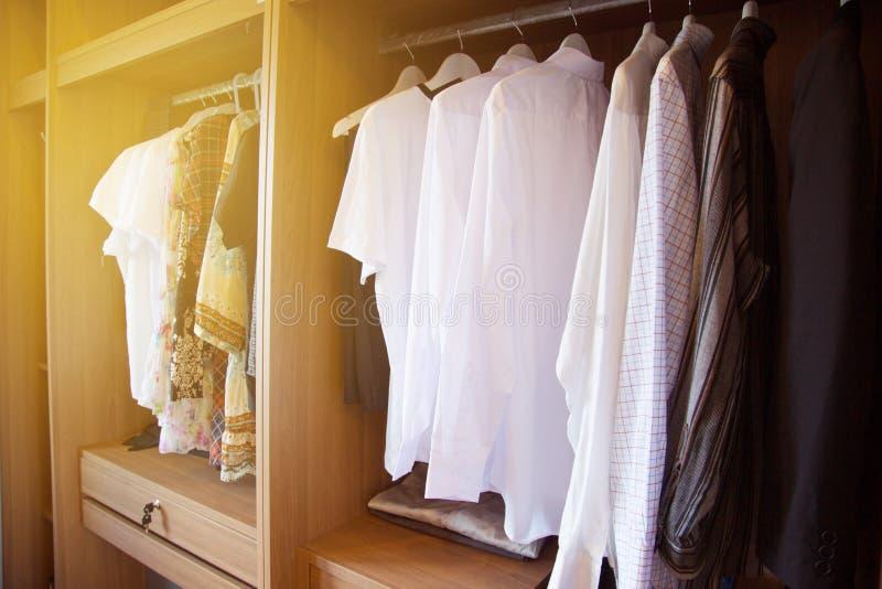 De kleren hangen op een plank in een ontwerper kleden opslag, Moderne kast met rij van kleren die in garderobe, Uitstekende ruimt royalty-vrije stock afbeelding