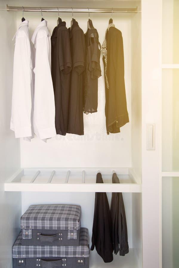 De kleren hangen op een plank in een ontwerper kleden opslag, Moderne kast met rij van kleren die in garderobe, Uitstekende ruimt stock afbeelding