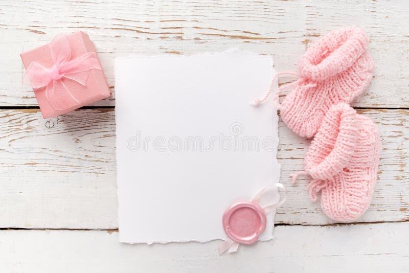 De kleren van het babymeisje, lege kaart met wasverbinding en kleine huidige doos op witte houten achtergrond Vlak leg Owerhadmen stock fotografie