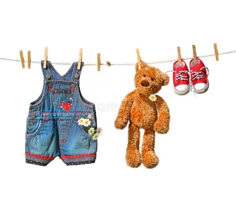 De kleren van het kind met teddybeer op drooglijn stock fotografie