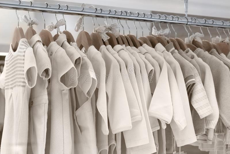 De kleren van kinderen van natuurlijke stoffen worden gemaakt hangen op hangers die stock afbeeldingen