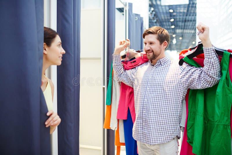 De kleren van de mensenholding voor vrouw in montageruimte stock foto