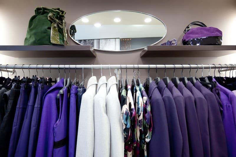 De kleren van modieuze vrouwen op hangers in winkel royalty-vrije stock afbeelding