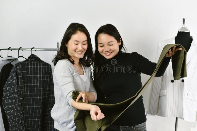 De kleren winkelen, het Aziatische manierontwerper werken in haar toonzaalstudio, Naaister aanpassend de beste kleur voor klant stock afbeelding