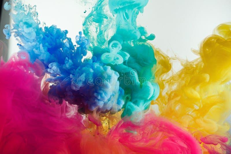 De kleurenplons van de inktregenboog in water stock foto