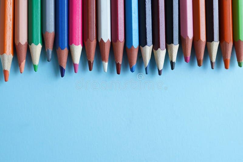 De kleurenpotloden op blauwe achtergrond sluiten omhoog Terug naar School royalty-vrije stock afbeeldingen