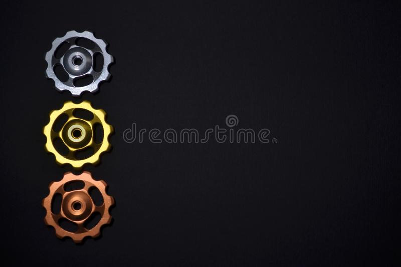 De kleurenrollen, zilveren, gouden, kopertoestellen voor fiets brengen derailleur op zwarte achtergrond in linkerkant, met copysp royalty-vrije stock afbeelding