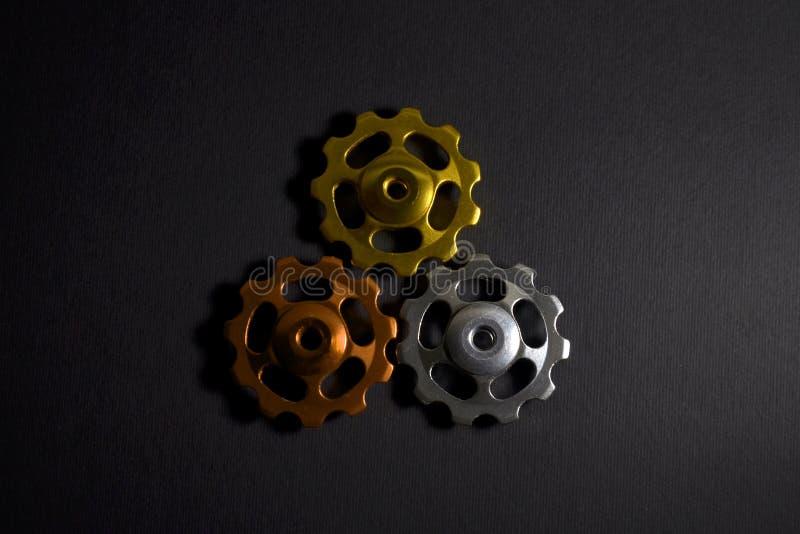 De kleurenrollen, zwarte, gouden, oranje toestellen voor fiets brengen derailleur op zwarte kleur in vorm van driehoek met schadu royalty-vrije stock afbeeldingen