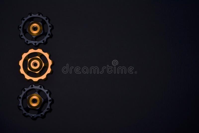 De kleurenrollen, zwarte, gouden toestellen voor fiets brengen derailleur op zwarte achtergrond in linkerkant, met copyspace groo royalty-vrije stock afbeeldingen