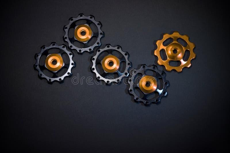 De kleurenrollen, zwarte, gouden toestellen voor fiets brengen derailleur op zwarte achtergrond met copyspace groot stock afbeeldingen