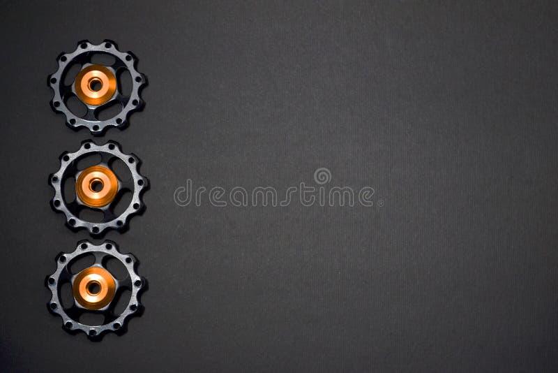 De kleurenrollen, zwarte, gouden toestellen voor fiets brengen derailleur op grijze achtergrond in linkerkant, met copyspace groo stock afbeeldingen