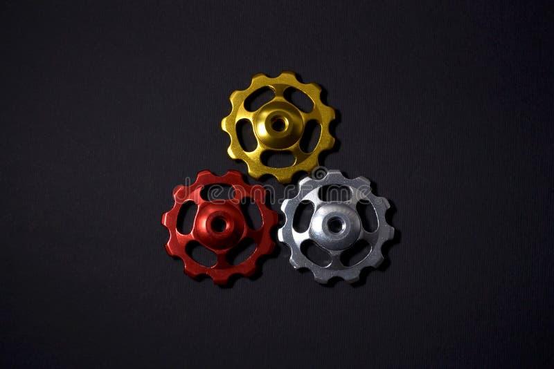 De kleurenrollen, zwarte, gouden, zilveren toestellen voor fiets brengen derailleur op zwarte kleur in vorm van driehoek met scha stock foto