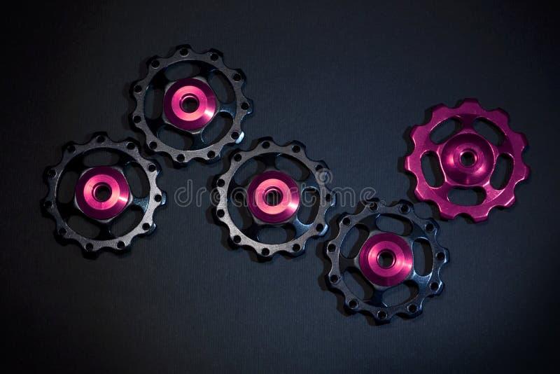 De kleurenrollen, zwarte, purpere toestellen voor fiets brengen derailleur op zwarte achtergrond groot stock foto