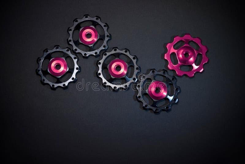 De kleurenrollen, zwarte, purpere toestellen voor fiets brengen derailleur op zwarte achtergrond met copyspace groot royalty-vrije stock fotografie