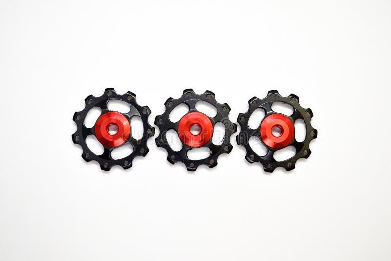 De kleurenrollen, zwarte, rode toestellen voor fiets brengen derailleur groot die op een witte achtergrond in midden, met copyspa stock afbeeldingen